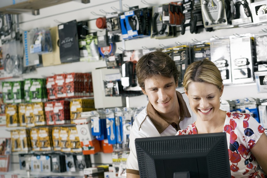Young couple looking at visual screen beside bike accessories display rack in bicycle shop, smiling